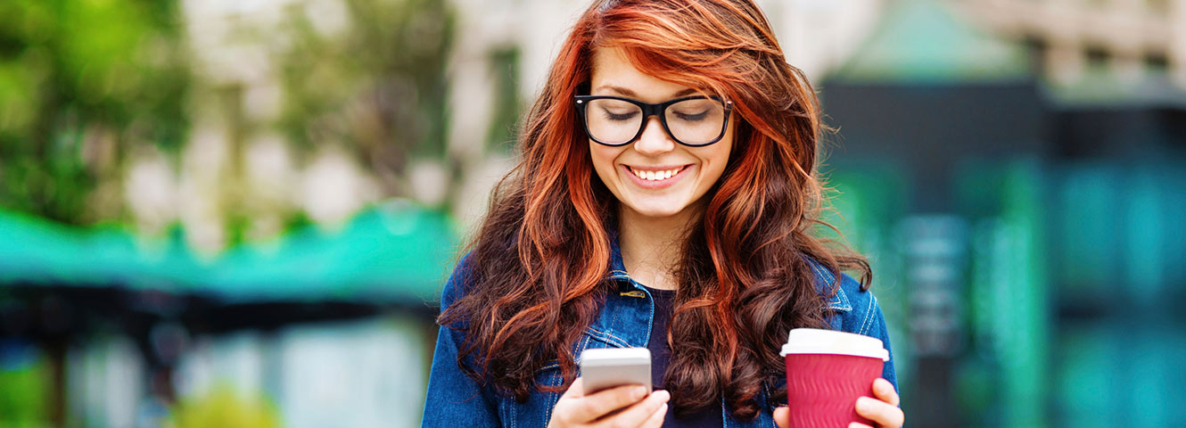Woman holding coffee and phone outdoors.